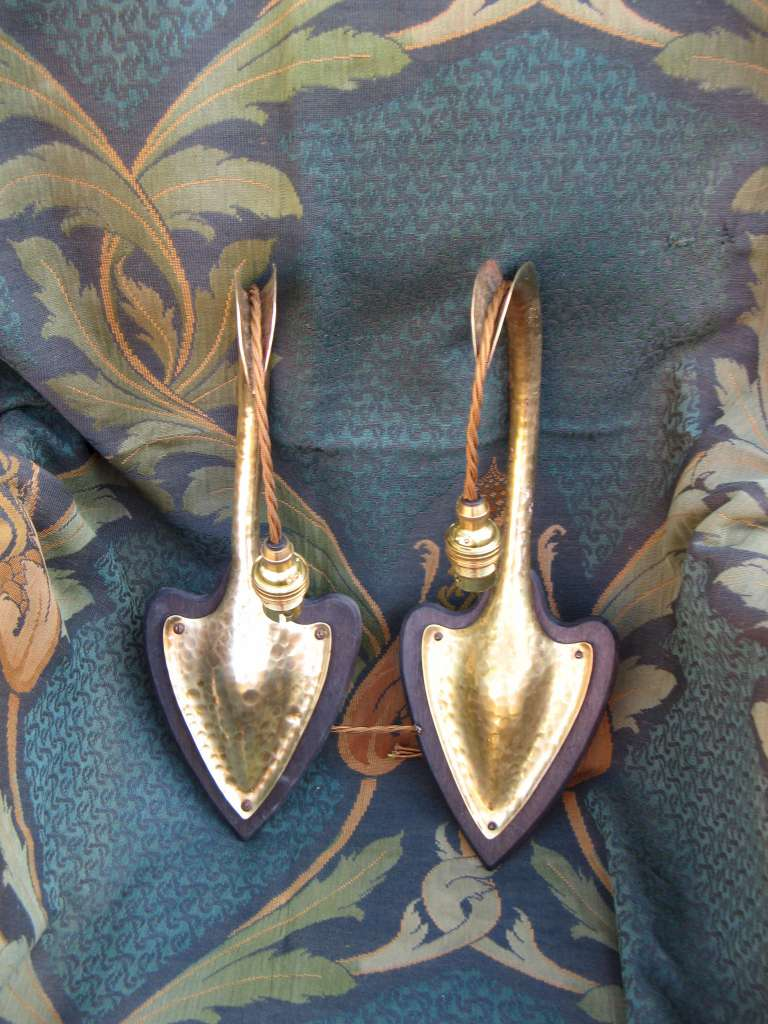 Pair of arts and crafts wall lights in hammered brass on wooden heart shaped backplates
