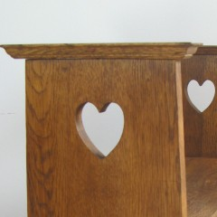 Arts and Crafts oak window seat with pierced heart cut outs.