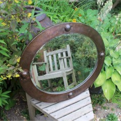 Arts and crafts oval copper mirror with raised roundels