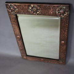 Arts and Crafts copper framed wall mirror with three stylised flower heads c1900