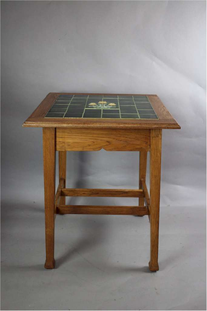 Arts and Crafts oak occasional table with tiled top.